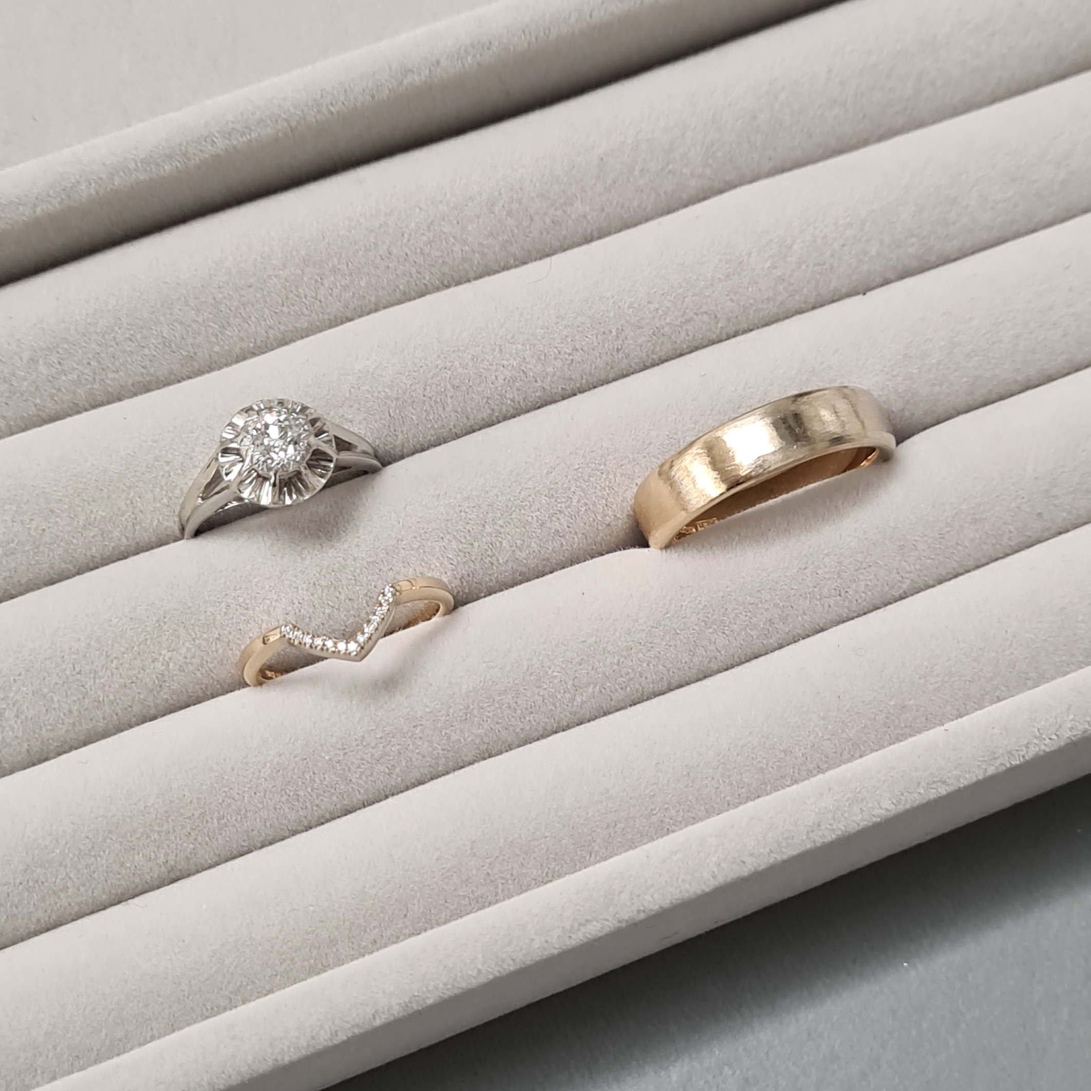 Three gold ring in a grey velvet tray.