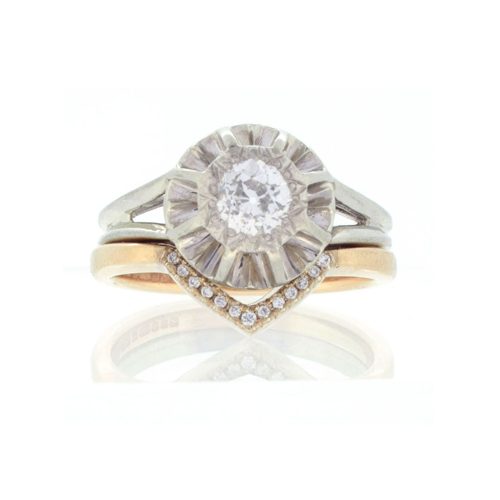 Vintage diamond engagement ring sitting on the bespoke fitted wedding band on a white background.