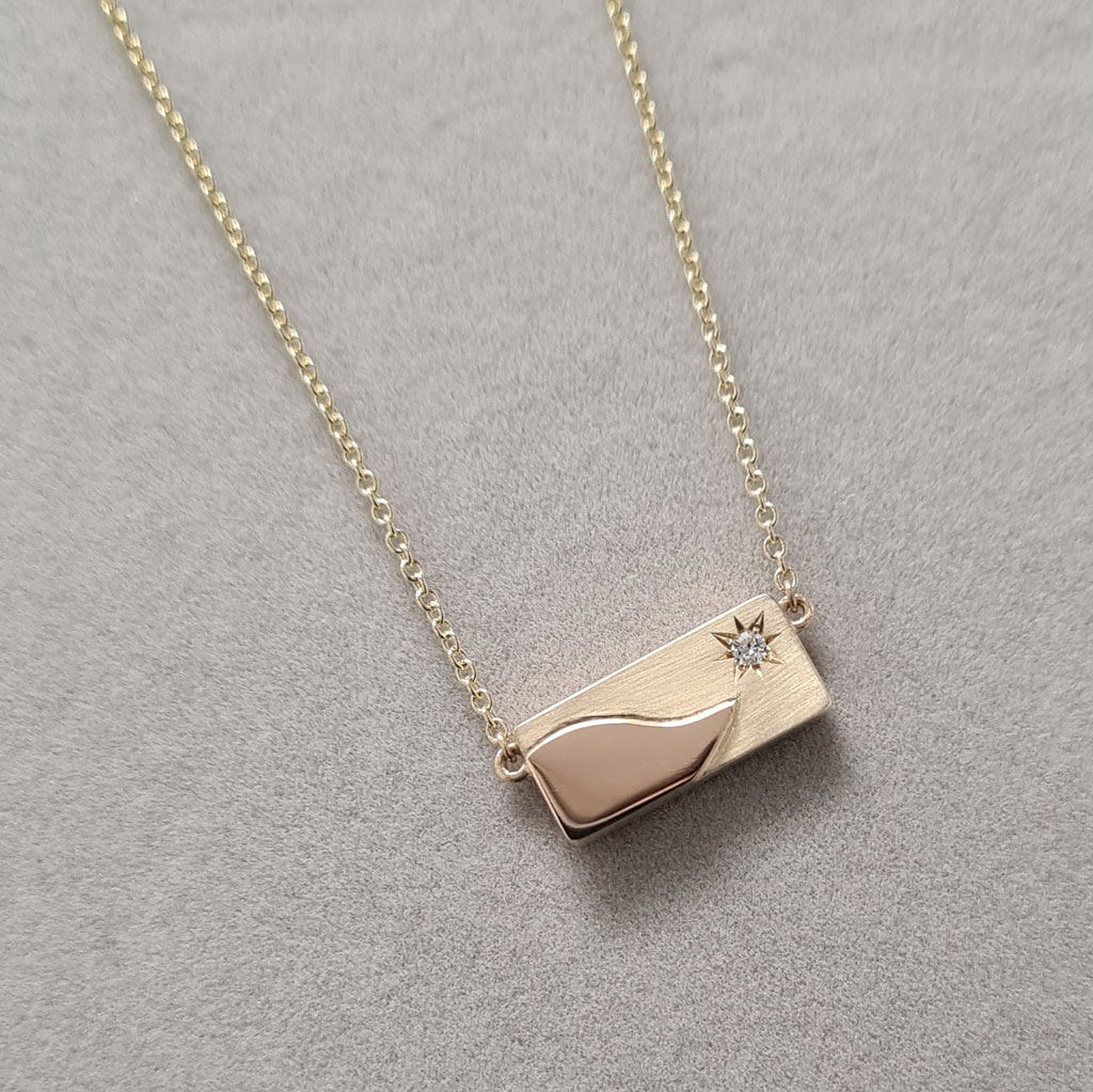 Rectangular memorial pendent in yellow gold with a rose gold and diamond hanging on a grey background.