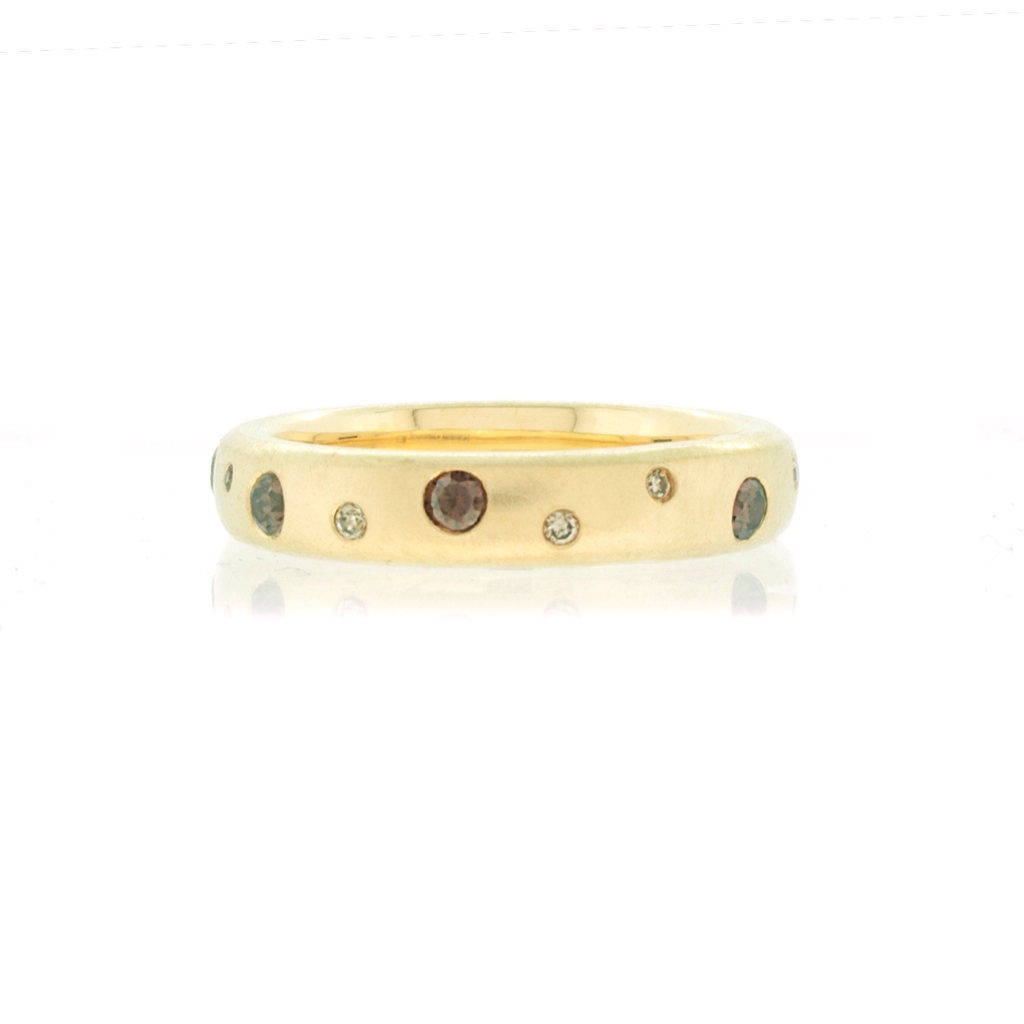 Yellow gold ring set with cognac and champagne diamonds laying on a white background.