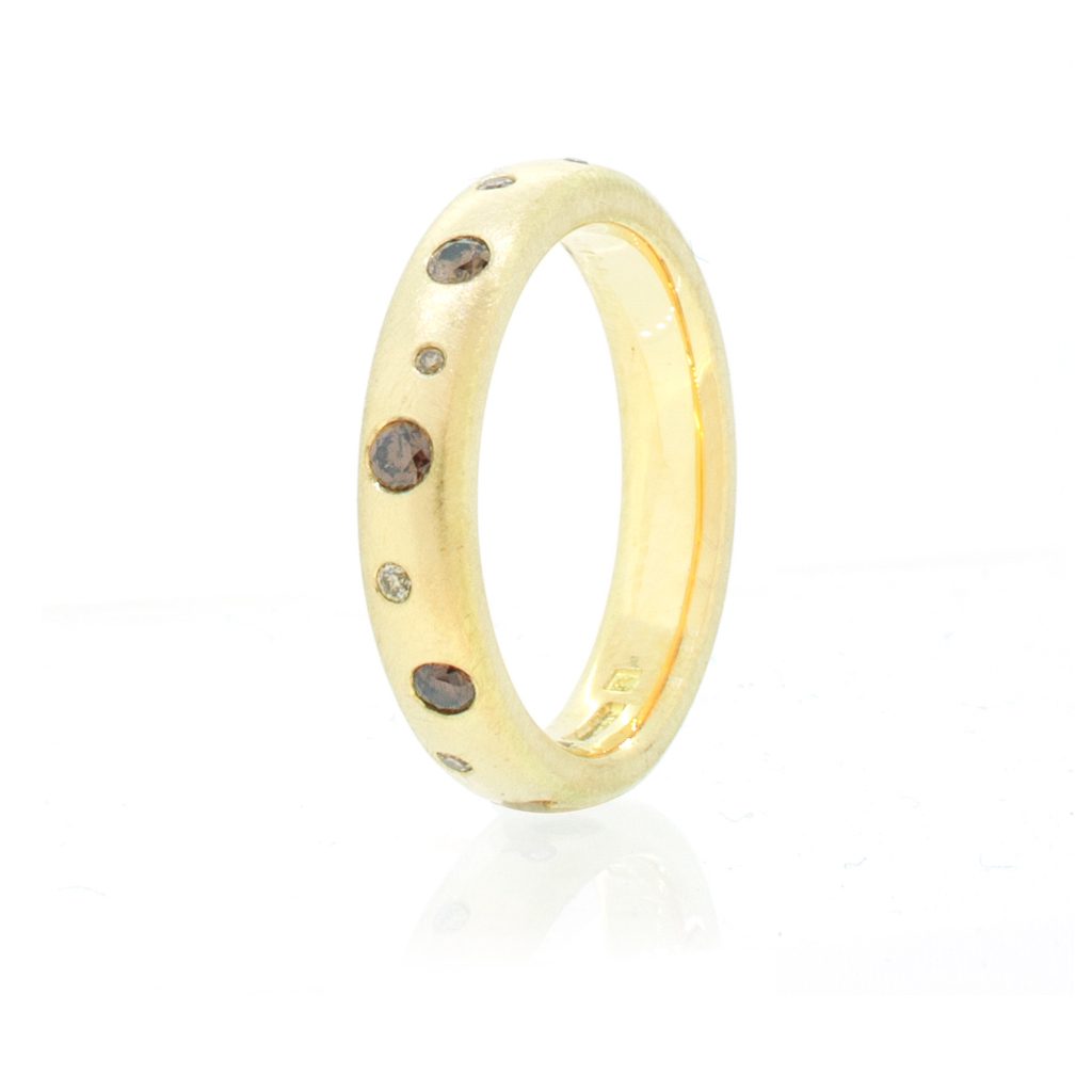 Yellow gold ring set with cognac and champagne diamonds standing upright on a white background.
