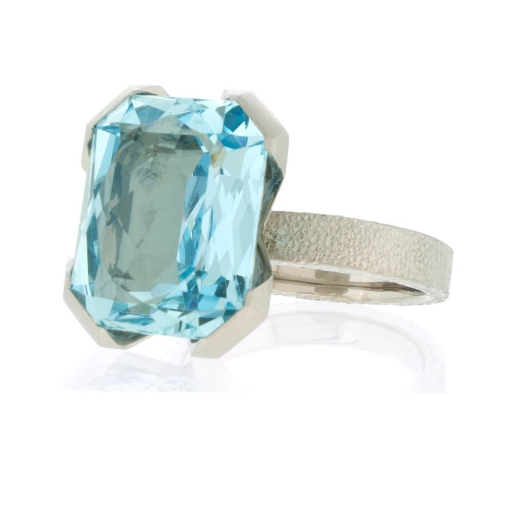 Aquamarine ring with offset stone laying down on a white background.