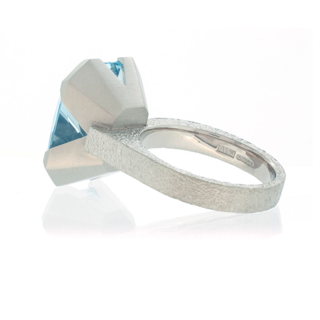 Underside view of an aquamarine ring with offset stone laying down on a white background.
