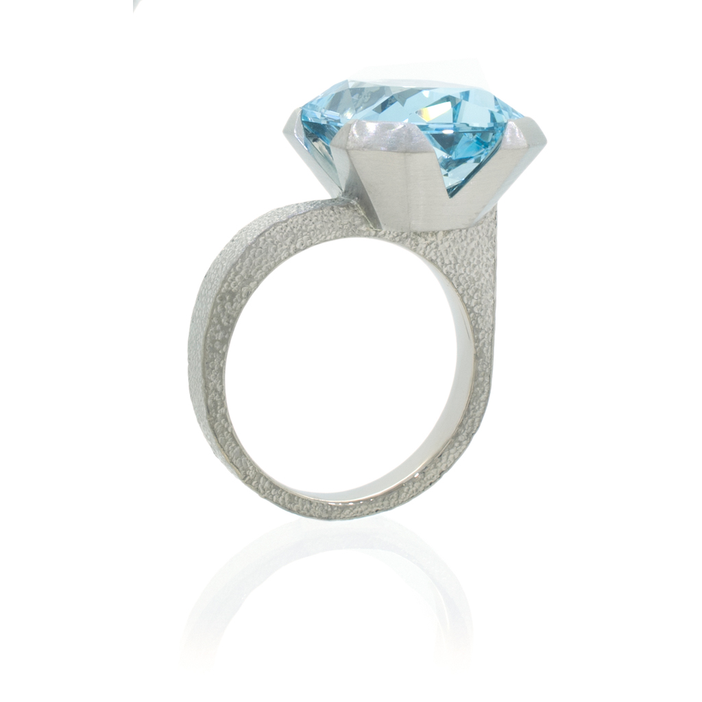 Aquamarine ring with offset stone standing upright on a white background.