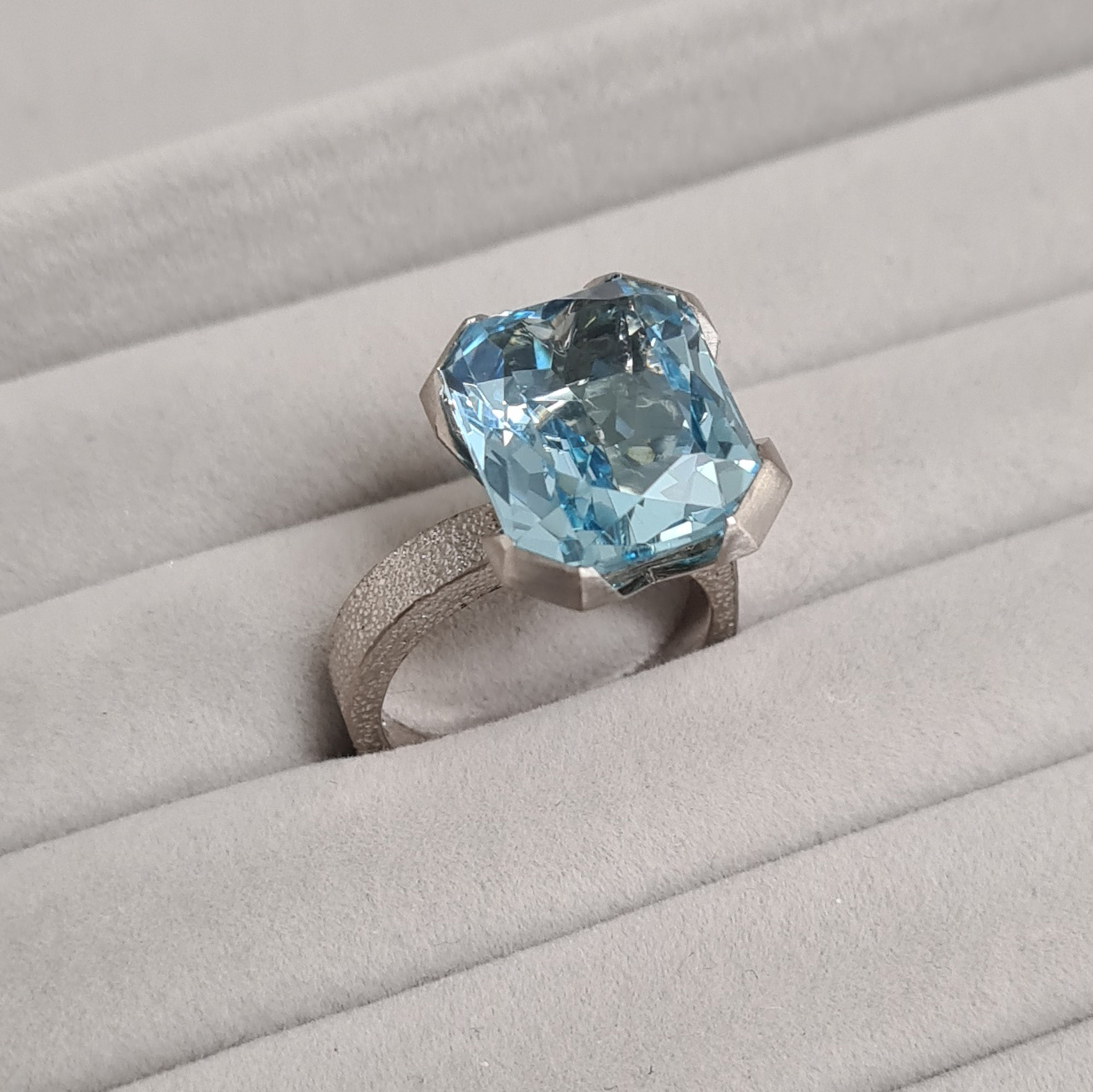 Aquamarine ring with offset stone sitting in a grey velvet ring tray.