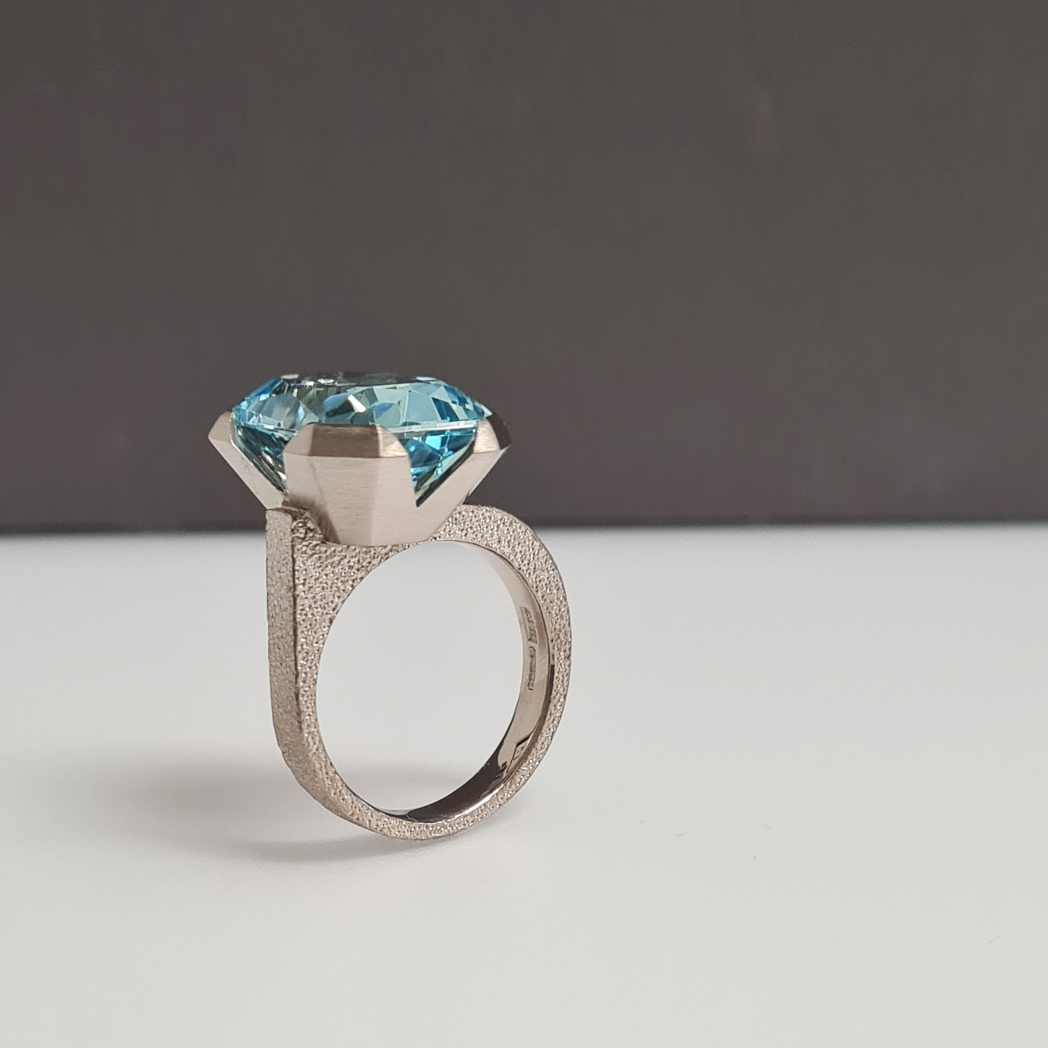 Aquamarine ring with offset stone standing upright with a grey background.