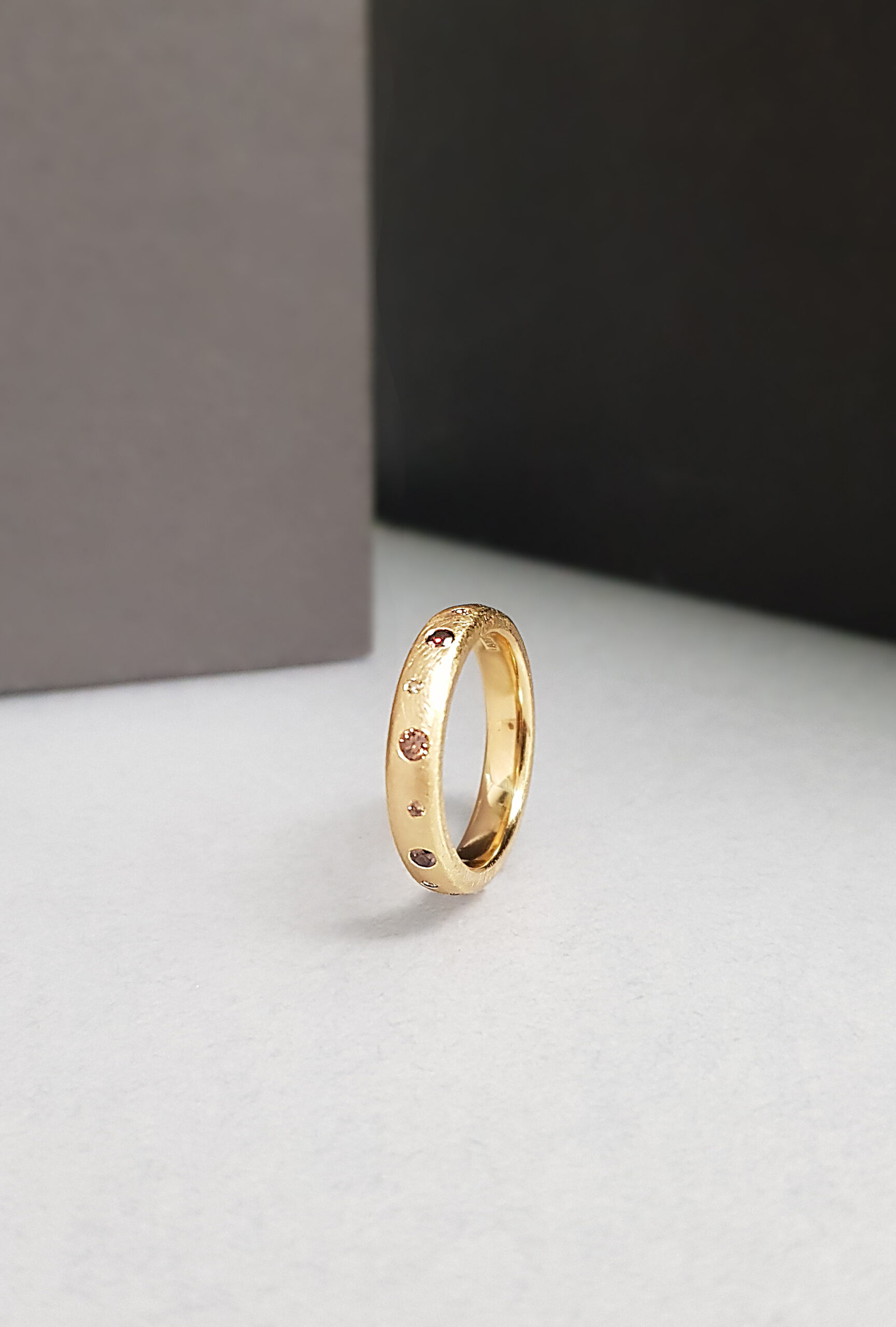 Yellow gold ring set with cognac and champagne diamonds standing upright on a white , grey and black background.