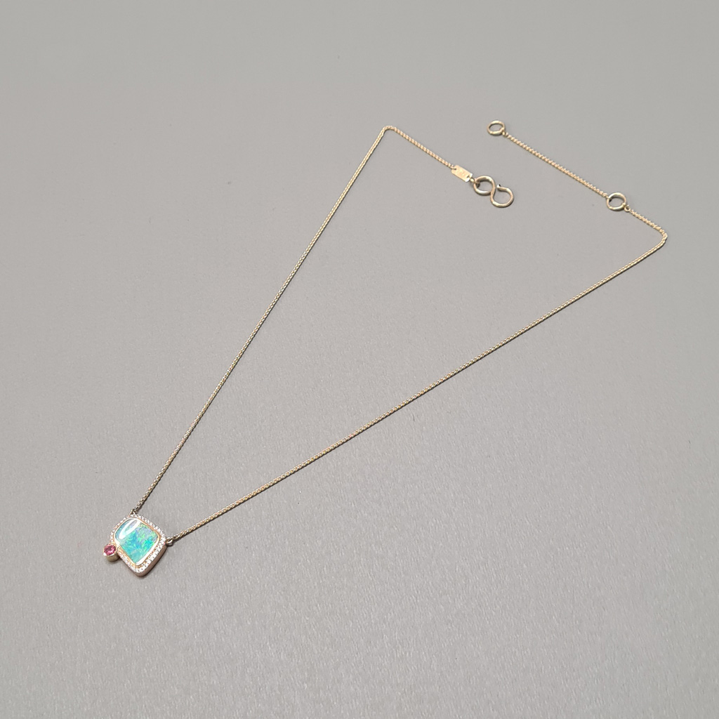 Opal, diamond, Freeform boulder opal with diamond halo in 18k yellow rose gold with accent padparadscha sapphire necklace laying down on a grey background.