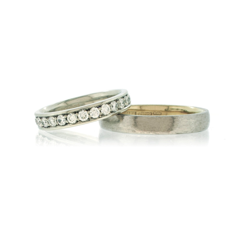 Platinum and diamond eternity ring with bi-metal platinum men's wedding ring on a white background.