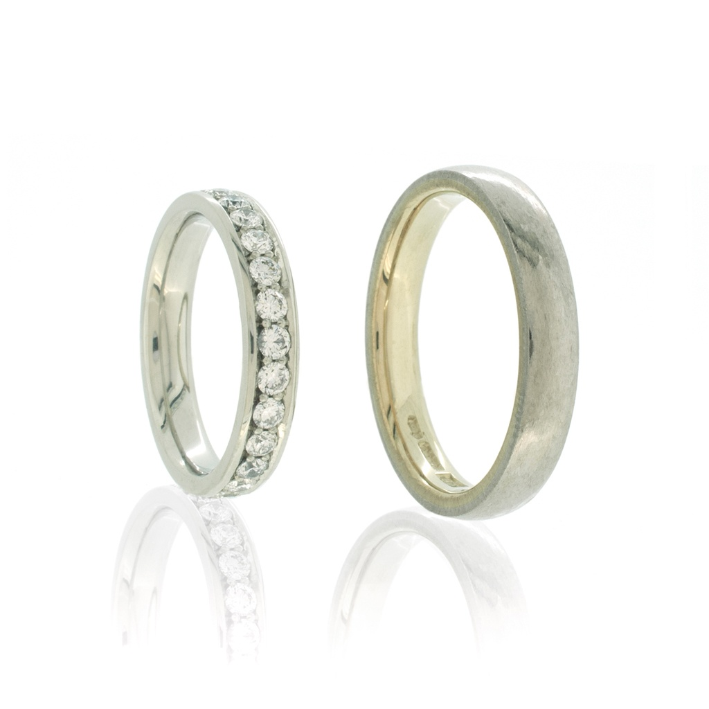 Platinum and diamond eternity ring with bi-metal platinum men's wedding ring standing upright on a white background.