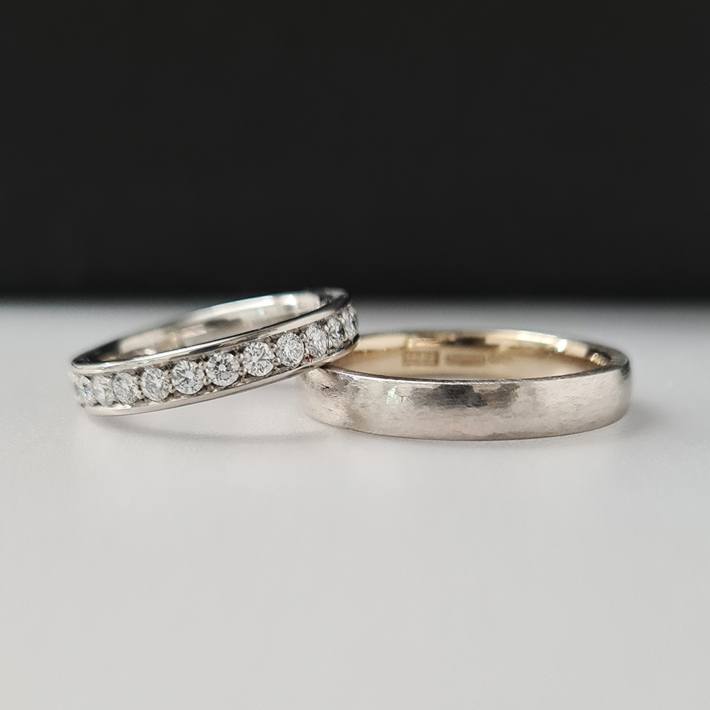 Women's eternity ring with lab-grown diamonds in recycled platinum and men's wedding band in 18k white gold and platinum with concentric ring design.### Platinum and diamond eternity ring and bi-metal platinum men's wedding ring laying down on white card with a black background.