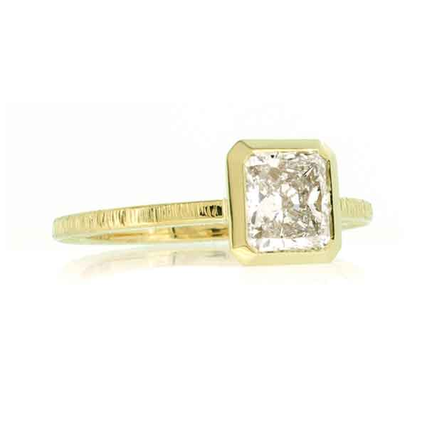 Radiant cut diamond solitaire ring in yellow gold on a white background.