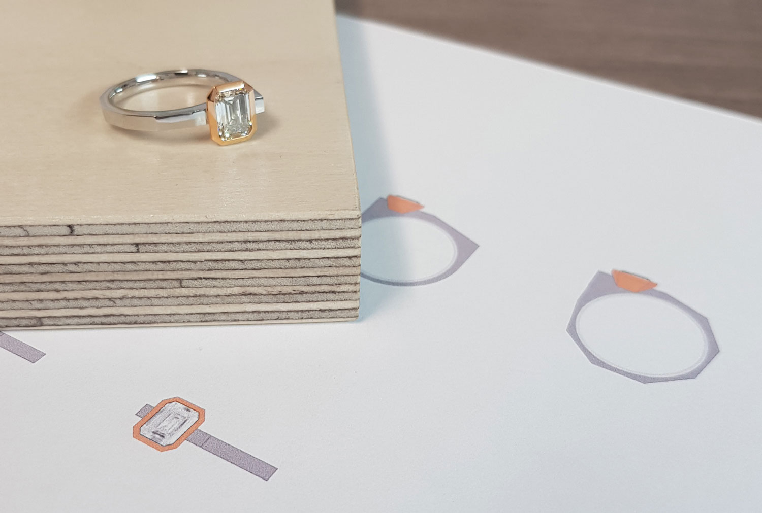 Platinum and gold engagement ring set with an emerald cut diamond shown with design sketches.
