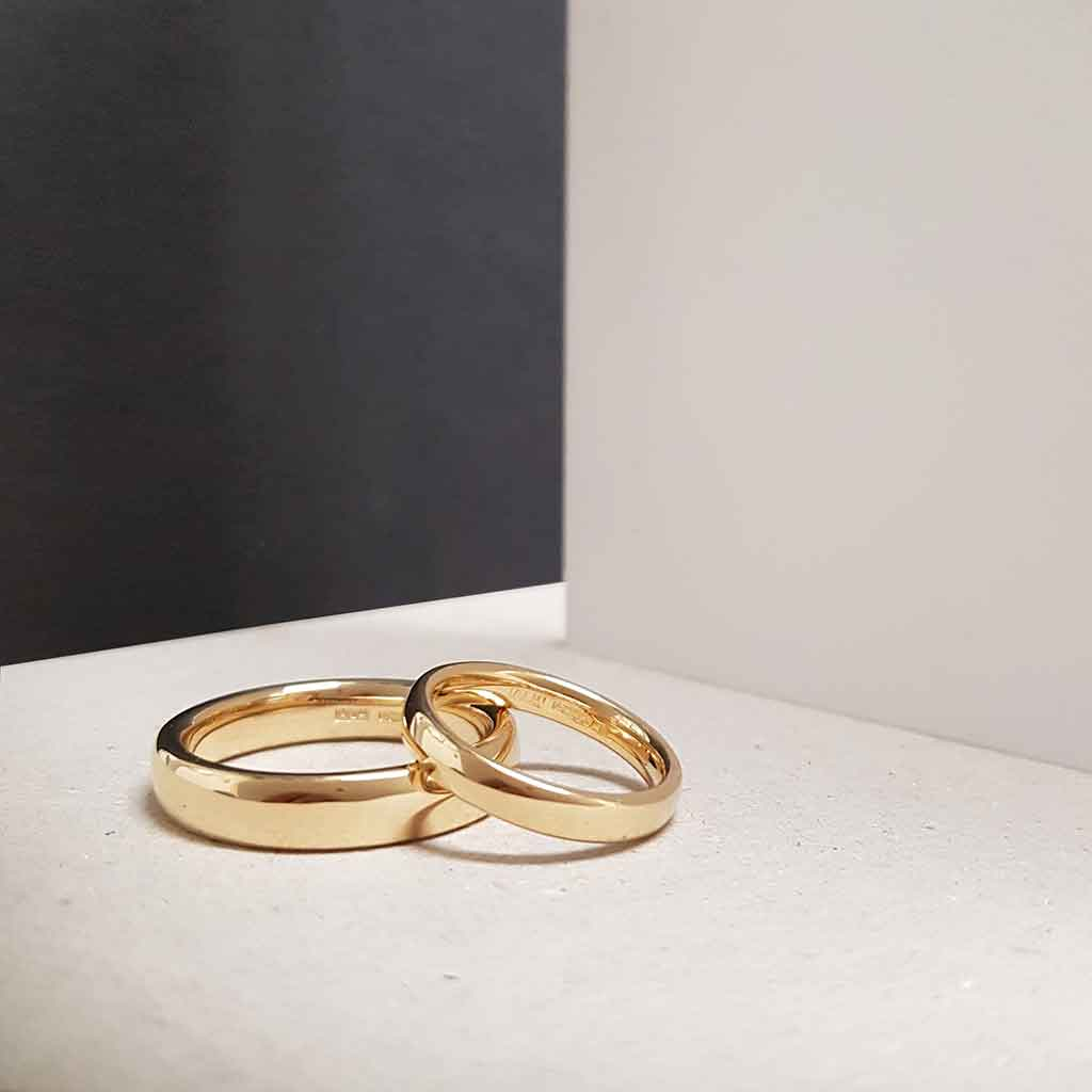 Two bespoke ethical wedding rings in light rose gold are stacked on top of one another, on a white surface set against a black and white colour-block background