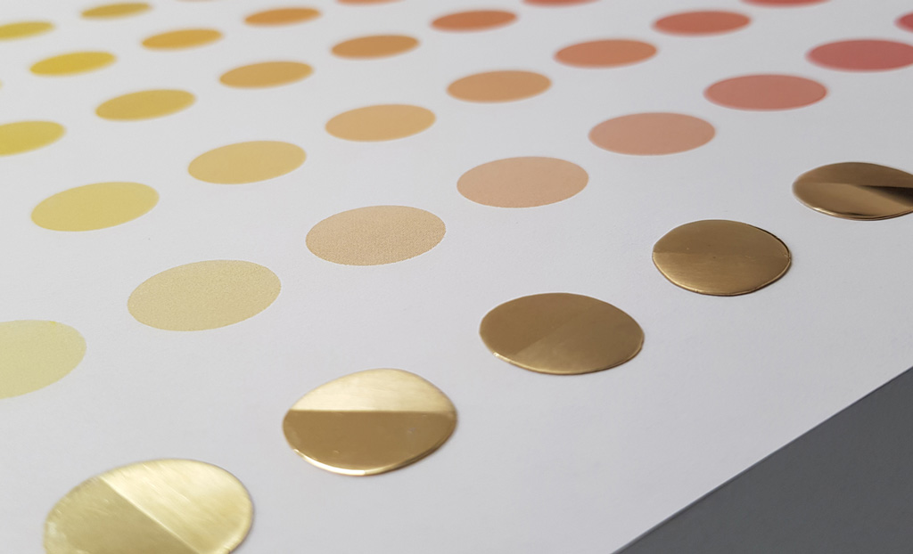 18ct gold colour swatches laid out on a grid of matching coloured dots printed on sheet of white paper.