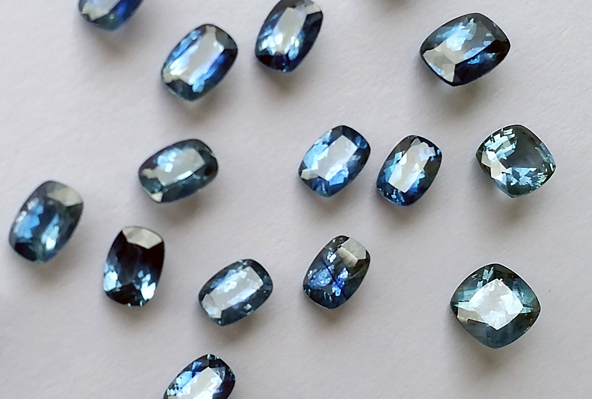 Scattered blue and teal cushion cut sapphires on a grey background.