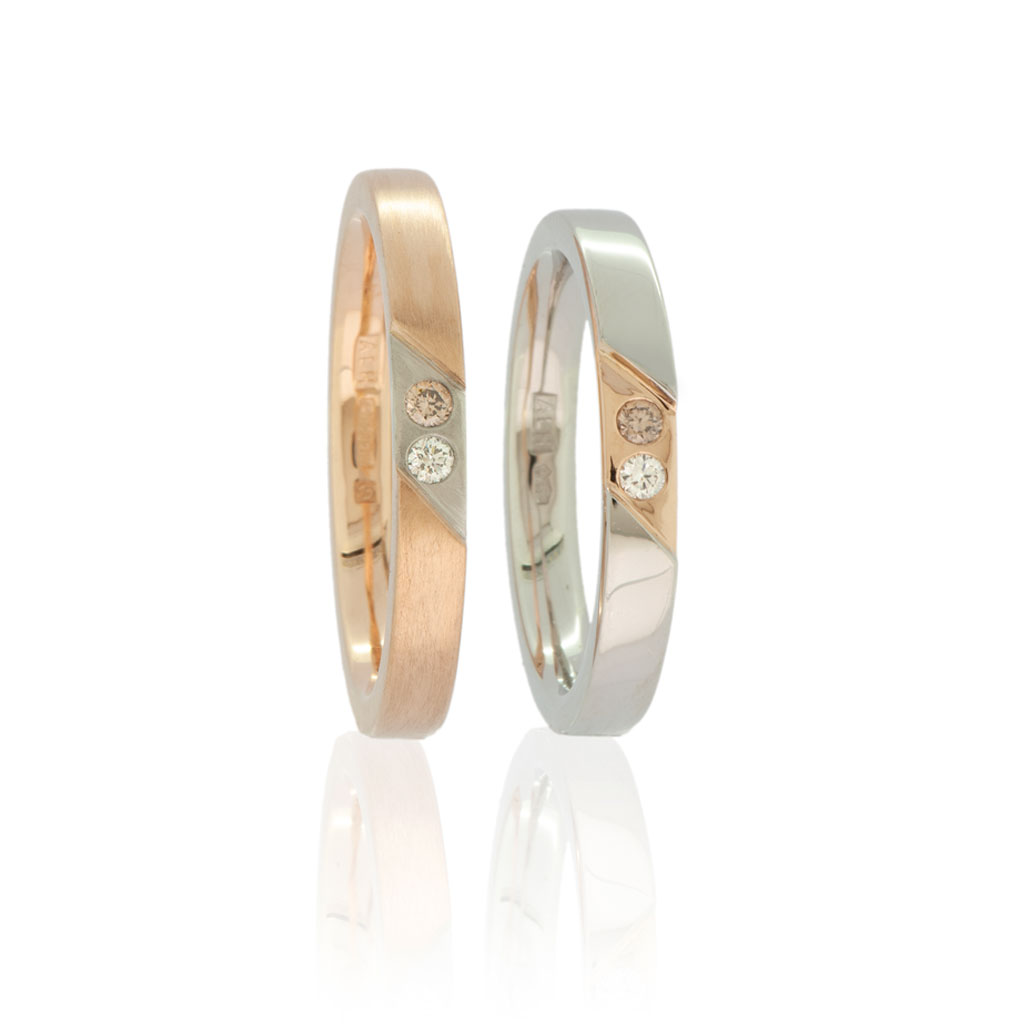Two rings in rose gold and platinum with inset colourless and champagne diamonds standing upright on a white background.