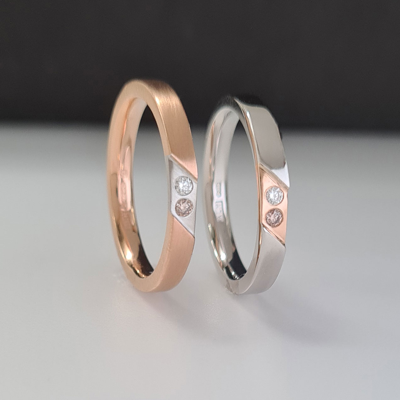 Two rings in rose gold and platinum with inset colourless and champagne diamonds standing upright on a black and white background.
