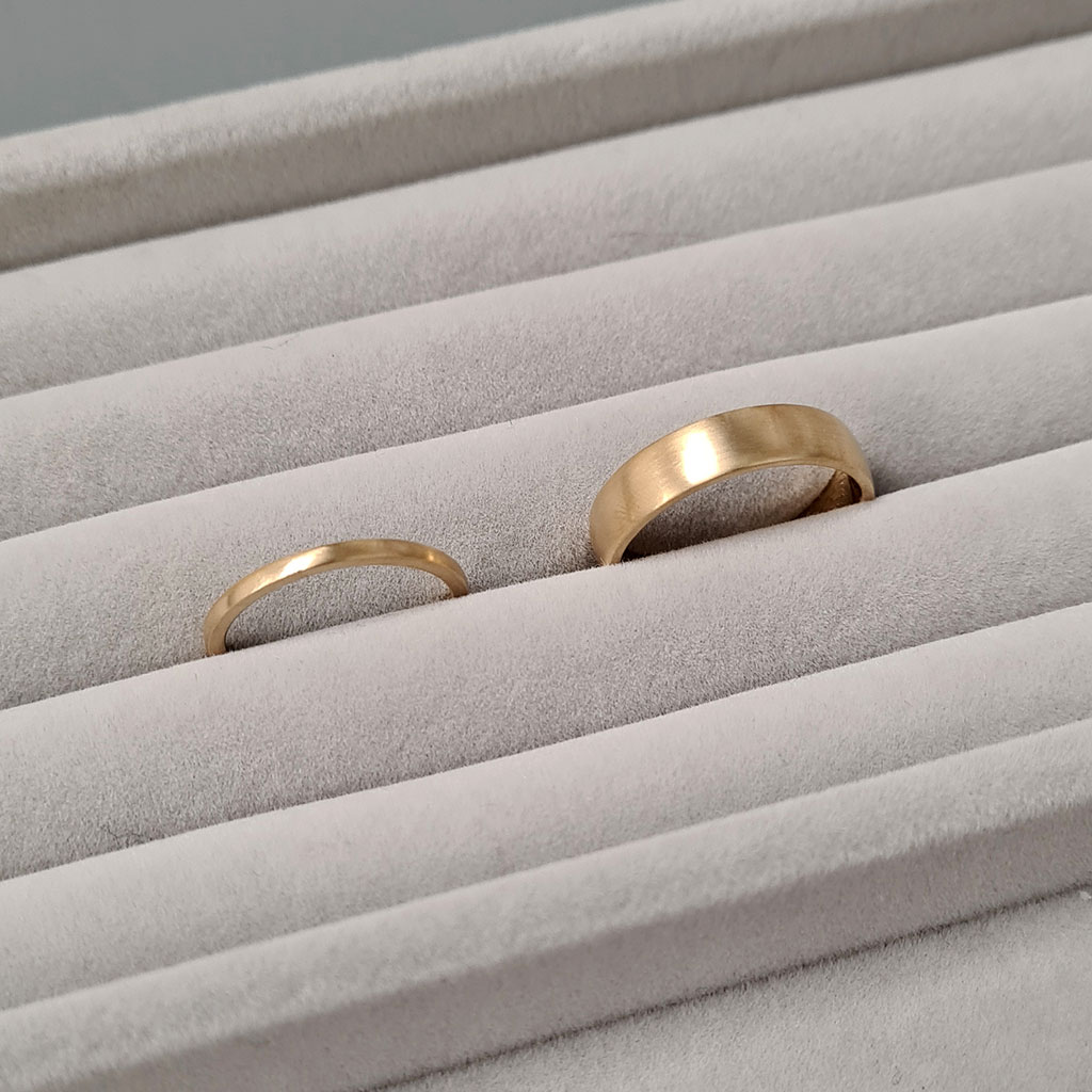 A pair of blush 18ct yellow gold wedding rings with a matte finish on a white background.