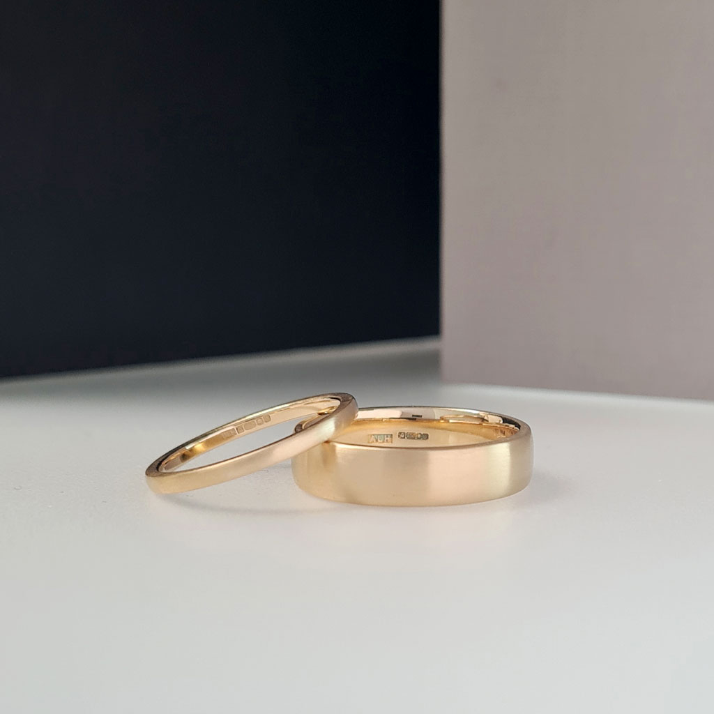 A pair of 18ct blush yellow gold wedding rings with a matte finish on a colour block background.