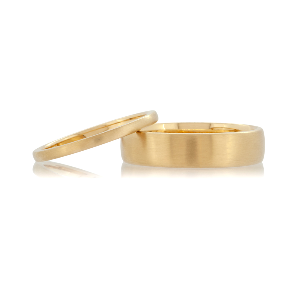 A pair of 18ct blush yellow gold wedding rings with a matte finish on a white background.