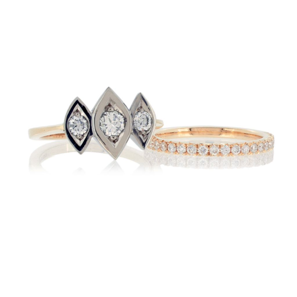 A trinity diamond ring with three diamonds in navette shaped white gold settings on a light rose gold band on a white background.