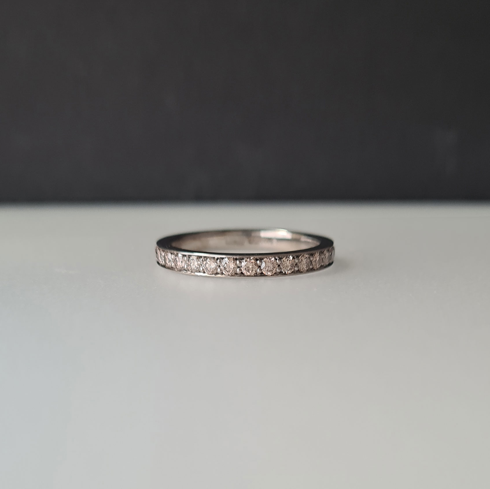 Champagne diamond eternity ring in white Fairtrade gold laying down flat on a black and white background.