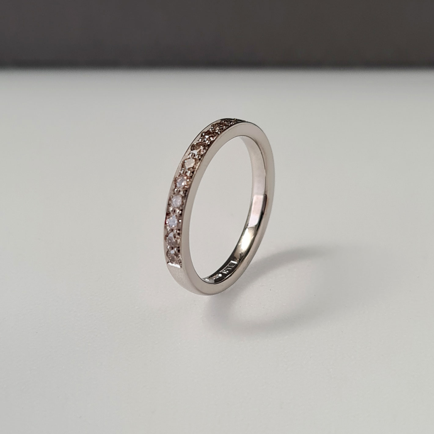 Champagne diamond eternity ring in white Fairtrade gold standing upright on a black and white background.