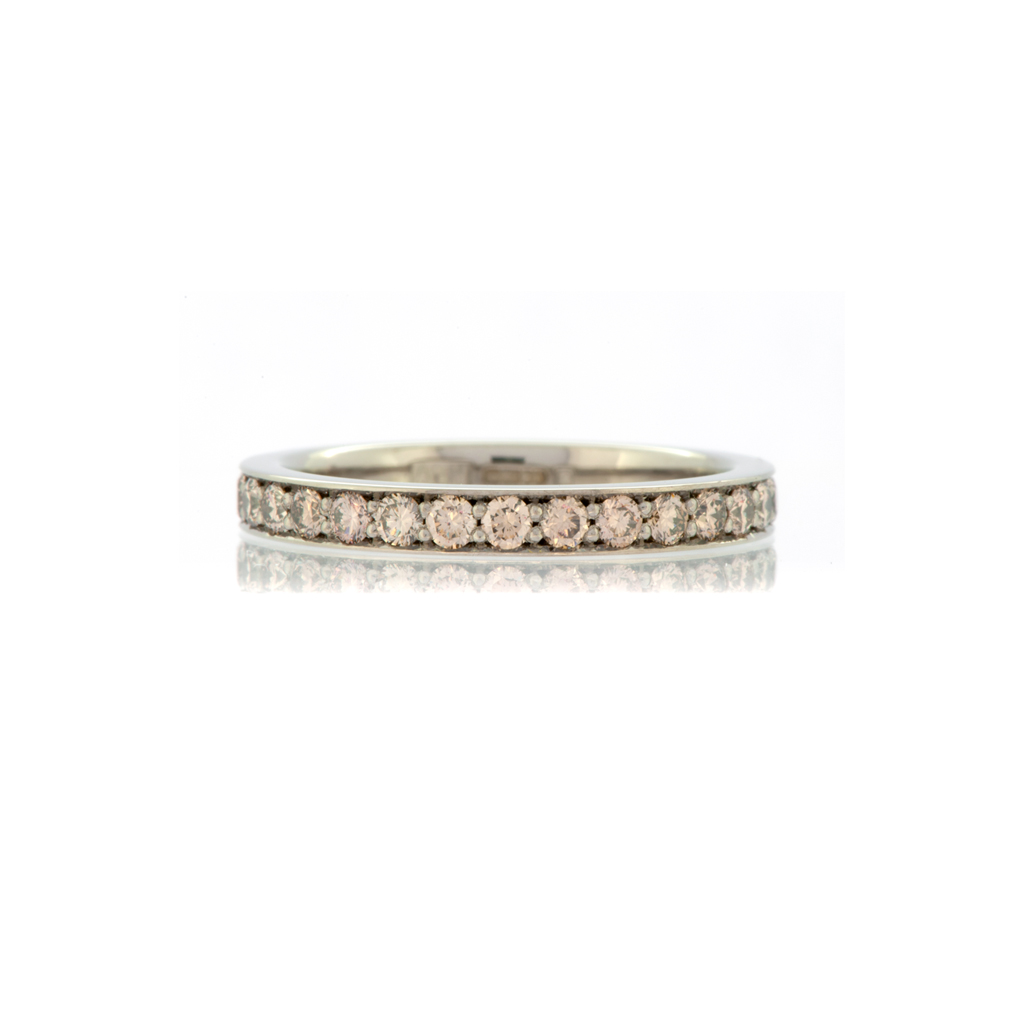 Champagne diamond eternity ring in white Fairtrade gold laying down flat on a white background.